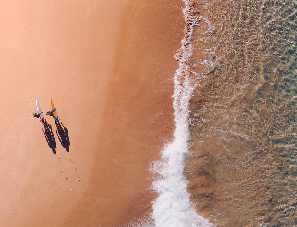 Surfers walking on beach